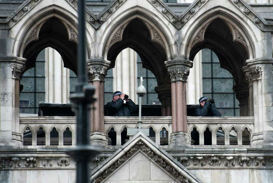 Police officers use binoculars as they keep watch from the Royal Courts of Justice during the ceremonial funeral of former prime minister Margaret Thatcher in central London on April 17, 2013. The funeral of Margaret Thatcher took place on April 17, with Queen Elizabeth II leading mourners from around the world in bidding farewell to one of Britain's most influential and divisive prime ministers.  AFP PHOTO / WILL OLIVERWILL OLIVER/AFP/Getty Images Photo: WILL OLIVER, AFP/Getty Images / AFP