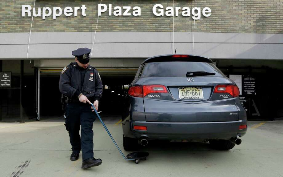 A police officer uses a mirror to check the undercarriage of a vehicle entering a nearby parking garage before a baseball game between the New York Yankees and Arizona Diamondbacks at Yankee Stadium in New York, Tuesday, April 16, 2013. Signs of increased security were visible around the stadium in the wake of the Boston Marathon explosions. Photo: Kathy Willens, AP / AP