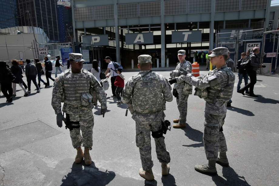 Security personnel stand in front of a PATH train station at the World Trade Center site in New York, Tuesday, April 16, 2013. Police armed with rifles and extra patrol cars were stationed around the city Tuesday as New York remained in a heightened state of alert until more is known about the Monday bombings at the Boston Marathon. Photo: Seth Wenig, AP / AP