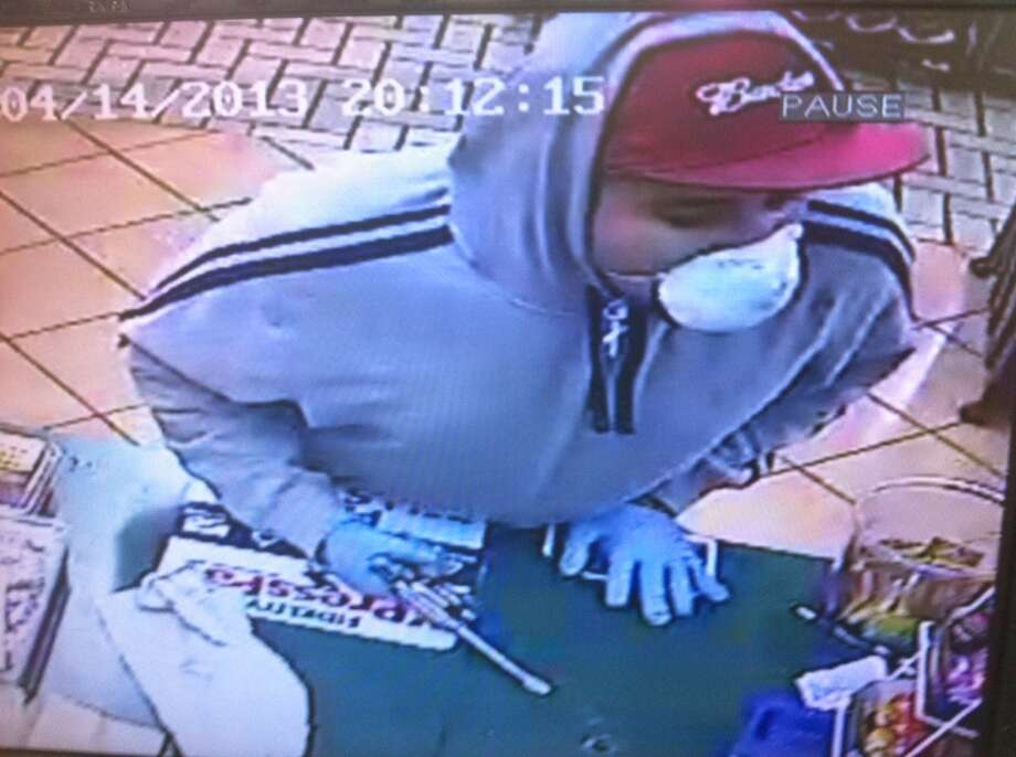 Crime Stoppers is offering a reward for information leading to the arrest of this man, who is shown here robbing the Trinity Food Mart on April 14.