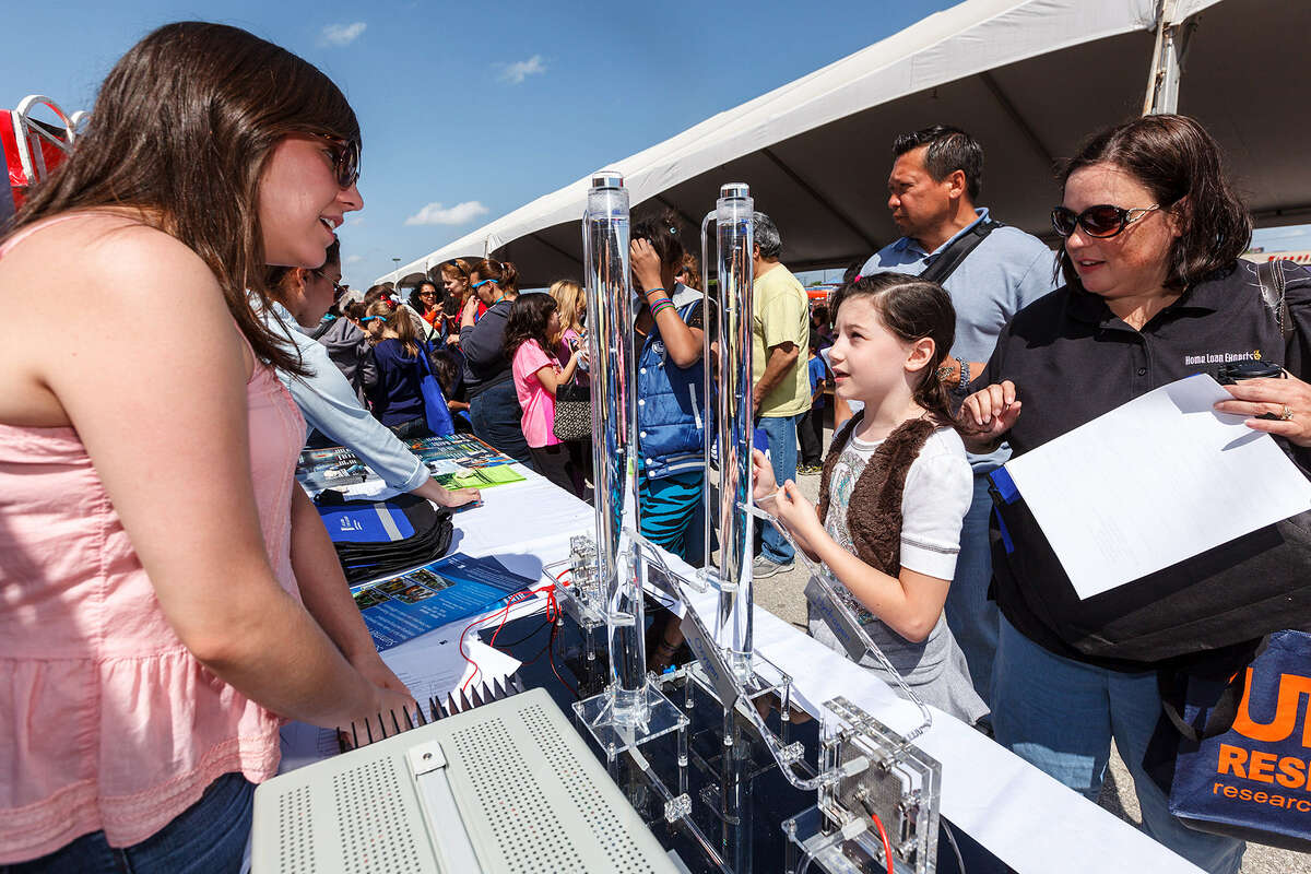 Audrie Cabrera (left) of St. Philip's College talks to Sarah Tope, 9, and her mother, Debbie, about fuel cells during the recent Girls Inc. Rockit into The Future Science Festival.