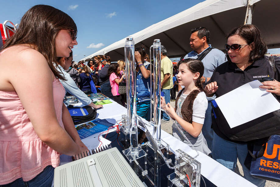 Audrie Cabrera (left) of St. Philip's College talks to Sarah Tope, 9, and her mother, Debbie,  about fuel cells during the recent Girls Inc. Rockit into The Future Science Festival. Photo: Marvin Pfeiffer / Express-News