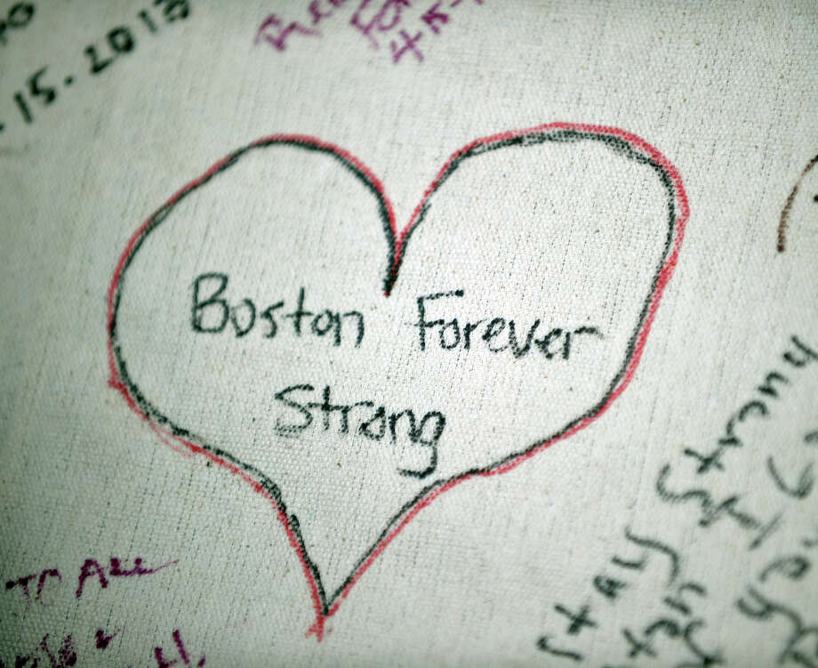 "A message written on a banner seen during a vigil on the Boston Common on April 16, 2013 in Boston, in the aftermath of two explosions that struck near the finish line of the Boston Marathon on April 15. Investigators said the range of suspects and motives in the grisly Boston bombings remained ""wide open"" as experts assessed remnants of the crude devices designed to inflict maximum suffering. Photo: STAN HONDA, AFP/Getty Images / 2013 AFP"