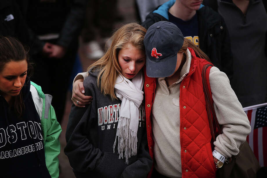 Two mourners hug during a vigil for victims of the Boston Marathon bombings at Boston Commons on April 16, 2013 in Boston, Massachusetts. The twin bombings, which occurred near the marathon finish line, resulted in the deaths of three people while hospitalizing at least 140. The bombings at the 116-year-old Boston race, resulted in heightened security across the nation with cancellations of many professional sporting events as authorities search for a motive to the violence. Photo: Spencer Platt, Getty Images / 2013 Getty Images