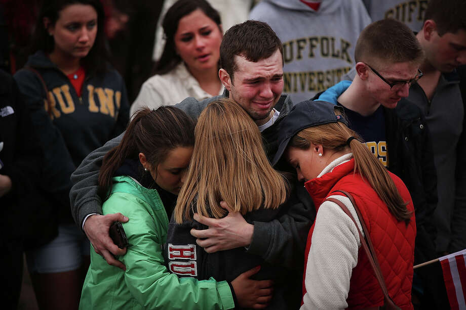 People hug and cry during a vigil for victims of the Boston Marathon bombings at Boston Commons on April 16, 2013 in Boston, Massachusetts. The twin bombings, which occurred near the marathon finish line, resulted in the deaths of three people while hospitalizing at least 140. The bombings at the 116-year-old Boston race, resulted in heightened security across the nation with cancellations of many professional sporting events as authorities search for a motive to the violence. Photo: Spencer Platt, Getty Images / 2013 Getty Images