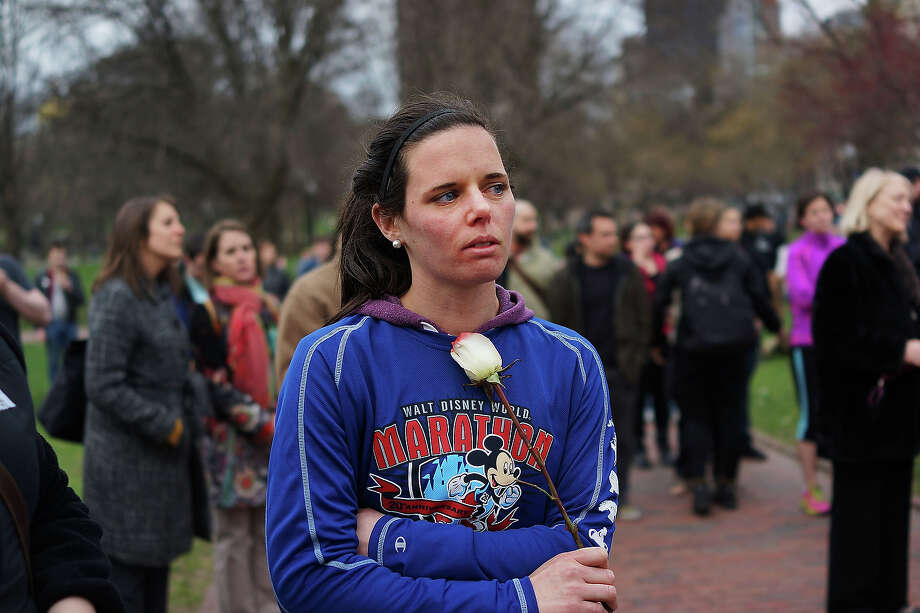 A woman holds a rose during vigil for victims of the Boston Marathon bombings at Boston Commons on April 16, 2013 in Boston, Massachusetts. The twin bombings, which occurred near the marathon finish line, resulted in the deaths of three people while hospitalizing at least 140. The bombings at the 116-year-old Boston race, resulted in heightened security across the nation with cancellations of many professional sporting events as authorities search for a motive to the violence. Photo: Spencer Platt, Getty Images / 2013 Getty Images