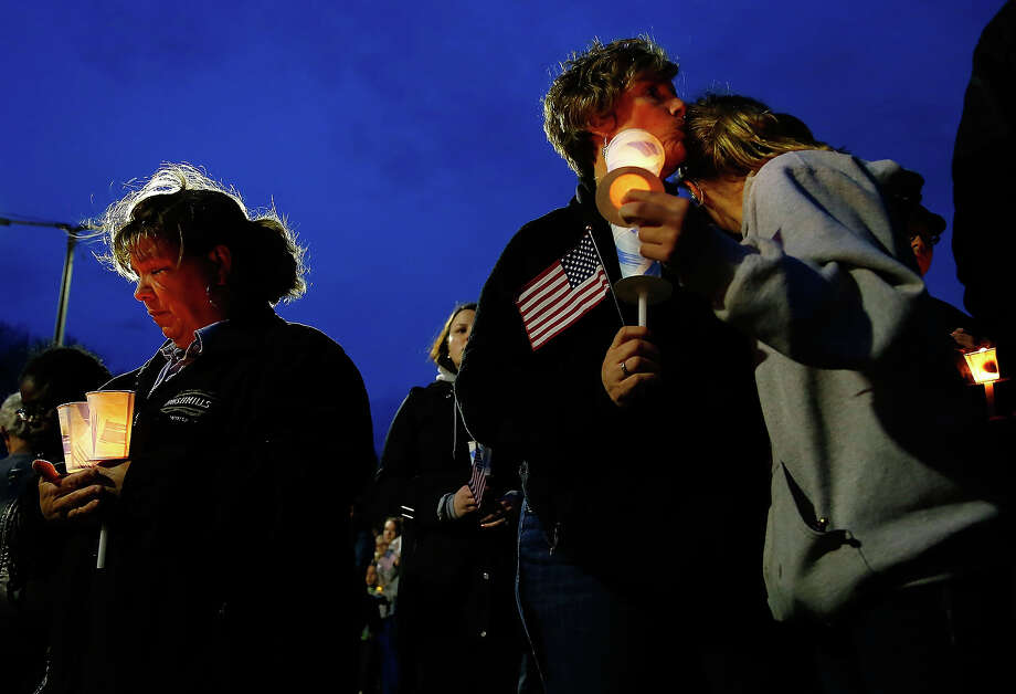A mother kisses her daughter on the head during a vigil for eight-year-old Martin Richard, from Dorchester, who was killed by an explosion near the finish line of the Boston Marathon on April 16, 2013 at Garvey Park in Boston, Massachusetts. The twin bombings resulted in the deaths of three people and hospitalized at least 128. The bombings at the 116-year-old Boston race resulted in heightened security across the nation with cancellations of many professional sporting events as authorities search for a motive to the violence. Photo: Jared Wickerham, Getty Images / 2013 Getty Images