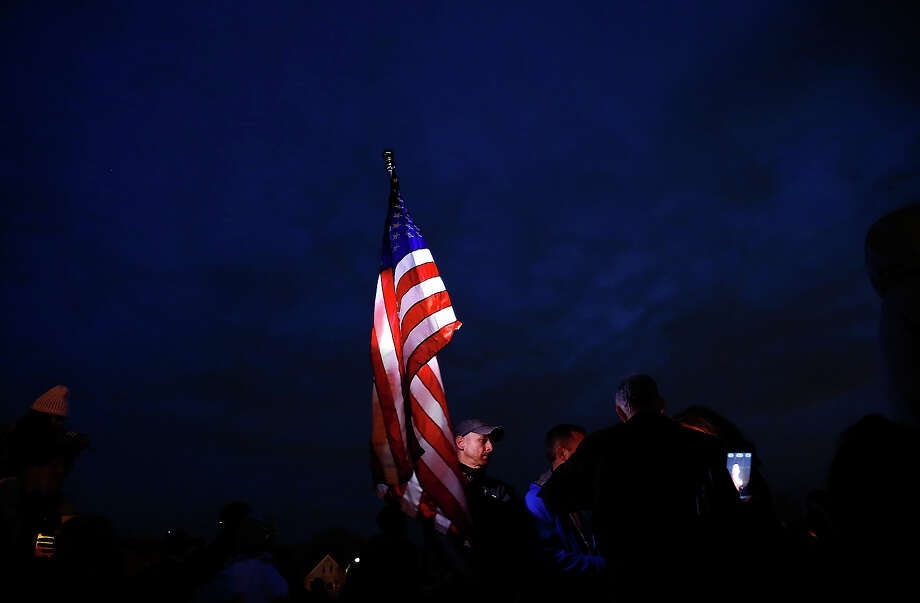 A man carries a large American flag during a vigil for eight-year-old Martin Richard, from Dorchester, who was killed by an explosion near the finish line of the Boston Marathon on April 16, 2013 at Garvey Park in Boston, Massachusetts. The twin bombings resulted in the deaths of three people and hospitalized at least 128. The bombings at the 116-year-old Boston race resulted in heightened security across the nation with cancellations of many professional sporting events as authorities search for a motive to the violence. Photo: Jared Wickerham, Getty Images / 2013 Getty Images