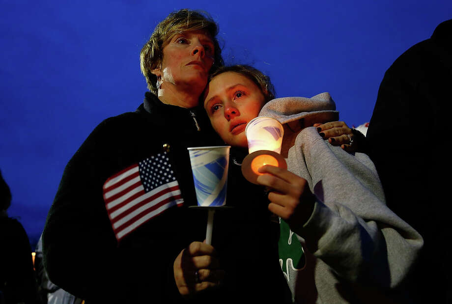 A young girl cries with her mother during the vigil for eight-year-old Martin Richard, from Dorchester, who was killed by an explosion near the finish line of the Boston Marathon on April 16, 2013 at Garvey Park in Boston, Massachusetts. The twin bombings resulted in the deaths of three people and hospitalized at least 128. The bombings at the 116-year-old Boston race resulted in heightened security across the nation with cancellations of many professional sporting events as authorities search for a motive to the violence. Photo: Jared Wickerham, Getty Images / 2013 Getty Images