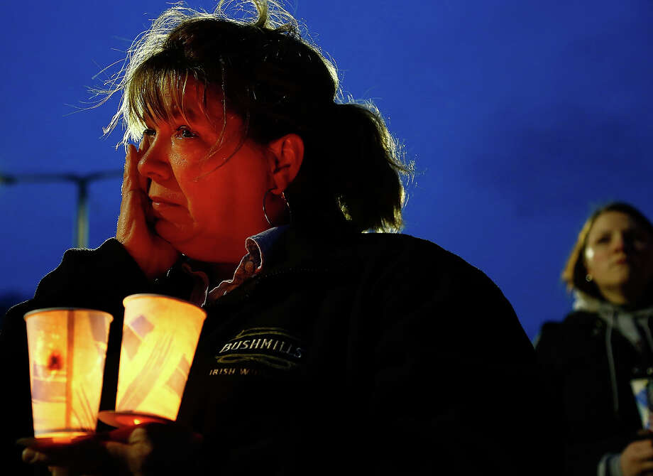 A woman cries while listening during the vigil for eight-year-old Martin Richard, from Dorchester, who was killed by an explosion near the finish line of the Boston Marathon on April 16, 2013 at Garvey Park in Boston, Massachusetts. The twin bombings resulted in the deaths of three people and hospitalized at least 128. The bombings at the 116-year-old Boston race resulted in heightened security across the nation with cancellations of many professional sporting events as authorities search for a motive to the violence. Photo: Jared Wickerham, Getty Images / 2013 Getty Images