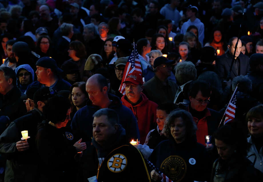 A man with an American flag on his hat attends a vigil for eight-year-old Martin Richard, from Dorchester, who was killed by an explosion near the finish line of the Boston Marathon on April 16, 2013 at Garvey Park in Boston, Massachusetts. The twin bombings resulted in the deaths of three people and hospitalized at least 128. The bombings at the 116-year-old Boston race resulted in heightened security across the nation with cancellations of many professional sporting events as authorities search for a motive to the violence. Photo: Jared Wickerham, Getty Images / 2013 Getty Images