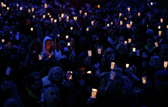 People gather with candles during a vigil for eight-year-old Martin Richard, from Dorchester, who was killed by an explosion near the finish line of the Boston Marathon on April 16, 2013 at Garvey Park in Boston, Massachusetts. The twin bombings resulted in the deaths of three people and hospitalized at least 128. The bombings at the 116-year-old Boston race resulted in heightened security across the nation with cancellations of many professional sporting events as authorities search for a motive to the violence. Photo: Jared Wickerham, Getty Images / 2013 Getty Images