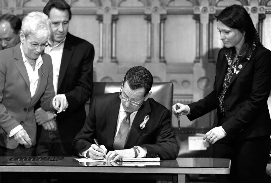 Connecticut Gov. Dannel P. Malloy, center, signs legislation at the Capitol in Hartford, Thursday, April 4, that includes new restrictions on weapons and large capacity ammunition magazines. The legislation adds more than 100 firearms to the state's assault weapons ban, sets eligibility rules for buying ammunition, and creates what officials have called the nation's first dangerous weapon offender registry. Photo: Steven Senne/AP Photo / Steven Senne/AP photo
