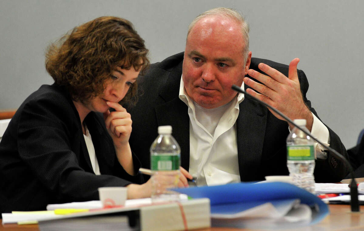 Michael Skakel, right, speaks to Jessica Santos, one of his defense attorneys, at Skakel's habeas corpus hearing at State Superior Court in Rockville, Conn., on Wednesday, April 17, 2013.