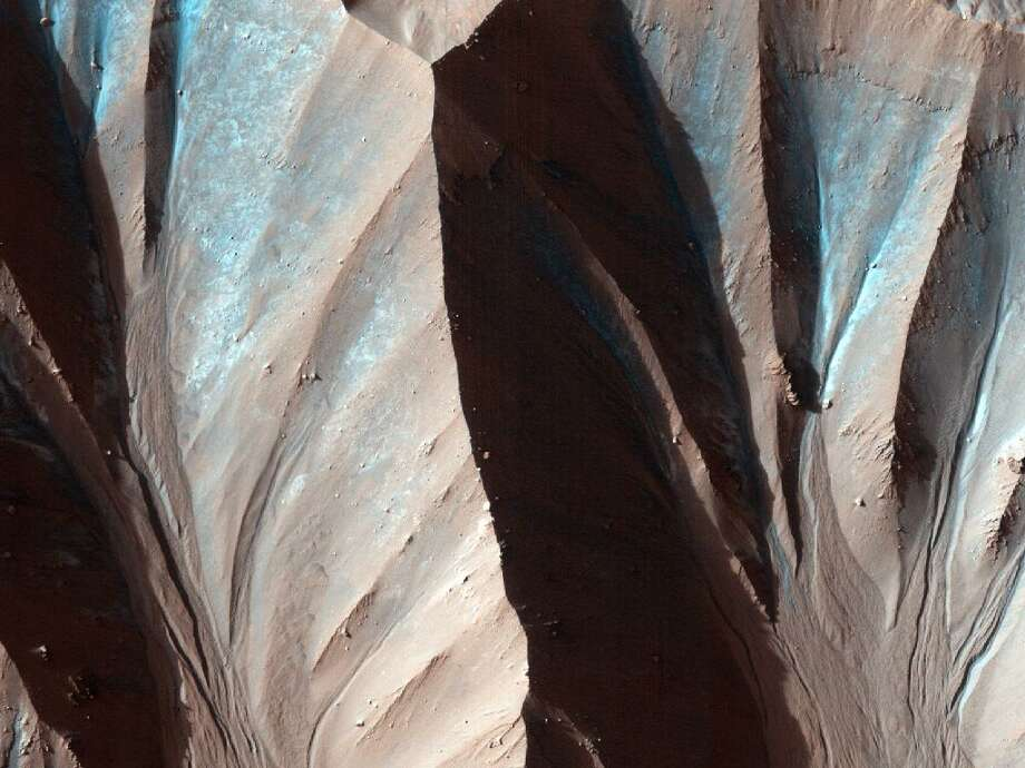 This image was taken by the High Resolution Imaging Science Experiment (HiRISE) flying onboard the Mars Reconnaissance Orbiter mission. Gully landforms like those in this image are found in many craters in the mid-latitudes of Mars. Photo: NASA