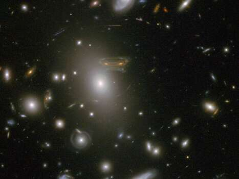 """The gravitational field surrounding this massive cluster of galaxies, Abell 68, acts as a natural lens in space to brighten and magnify the light coming from very distant background galaxies. In this photo, the image of a spiral galaxy at upper left has been stretched and mirrored into a shape similar to that of a simulated alien from the classic 1970s computer game """"Space Invaders!"""" A second, less distorted image of the same galaxy appears to the left of the large, bright elliptical galaxy. Photo: NASA"""