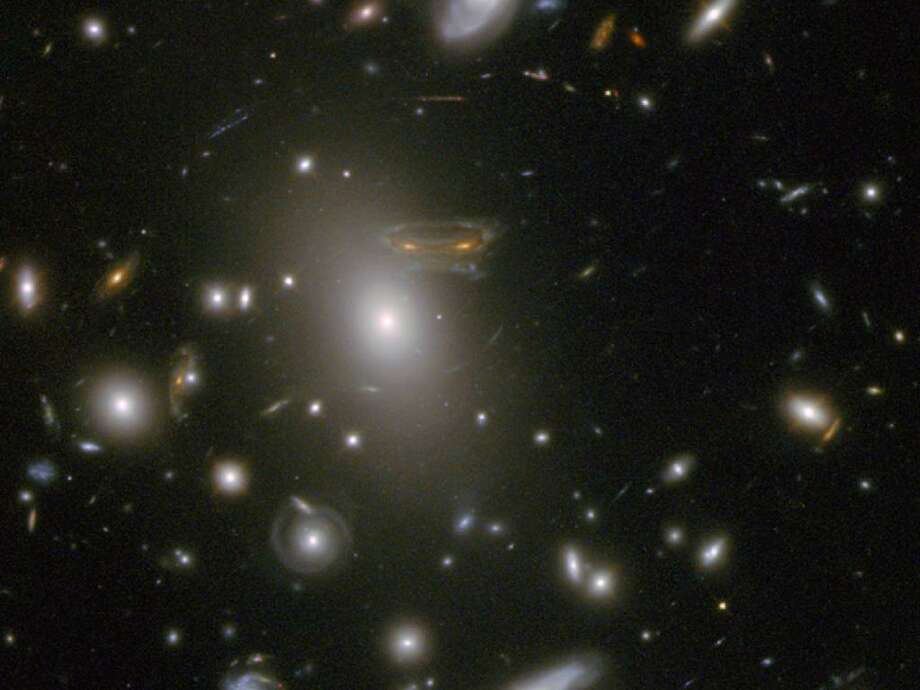"The gravitational field surrounding this massive cluster of galaxies, Abell 68, acts as a natural lens in space to brighten and magnify the light coming from very distant background galaxies. In this photo, the image of a spiral galaxy at upper left has been stretched and mirrored into a shape similar to that of a simulated alien from the classic 1970s computer game ""Space Invaders!"" A second, less distorted image of the same galaxy appears to the left of the large, bright elliptical galaxy. Photo: NASA"