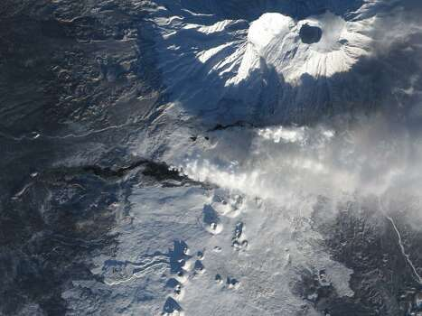 After more than a month of eruption, lava continues to flow from Tolbachik, one of many active volcanoes on Russia's Kamchatka Peninsula. The current eruption at Tolbachik began on Nov. 27, 2012. Lava flowed up to 20 kilometers (12 miles) from a line of fissures on the volcano's southern flank. Since then, some of the lava has cooled enough to allow snow to accumulate. Snow-covered lava flows appear gray in this natural-color satellite image. Fresher lava appears black. A faint orange glow at the head of the northern flow marks the location of an erupting fissure. Photo: NASA
