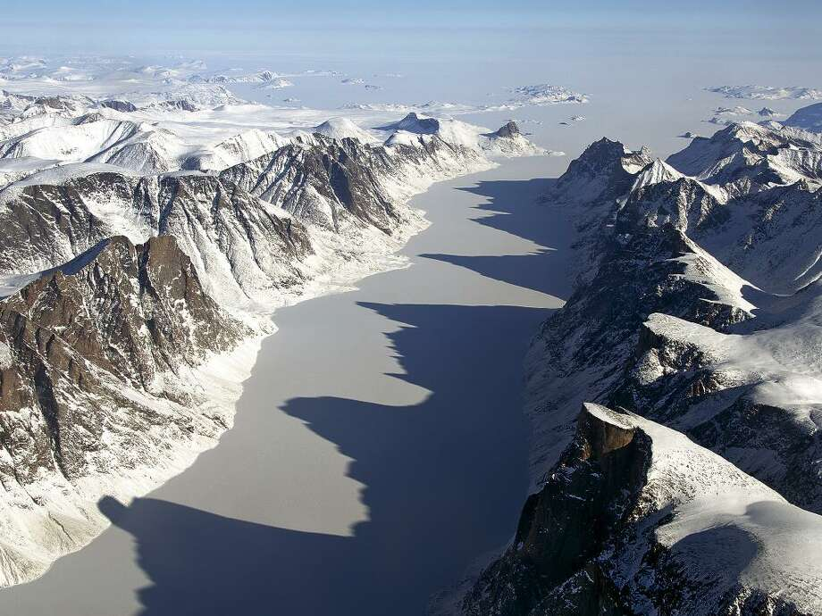 IceBridge Flight Over Baffin Island: The image captures ice covered fjord on Baffin Island with Davis Strait in the background. 