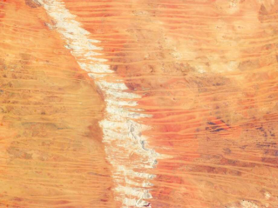 In northwest Australia, the Great Sandy Desert holds great geological interest as a zone of active sand dune movement. While a variety of dune forms appear across the region, this astronaut photograph features numerous linear dunes (about 25 meters high) separated in a roughly regular fashion (0.5 to 1.5 kilometers apart). The dunes are aligned to the prevailing winds that generated them, which typically blow from east to west. Where linear dunes converge, dune confluences point downwind. When you fly over such dune fields—either in an airplane or the International Space Station—the fire scars stand out. Where thin vegetation has been burned, the dunes appear red from the underlying sand; dunes appear darker where the vegetation remains. Photo: NASA