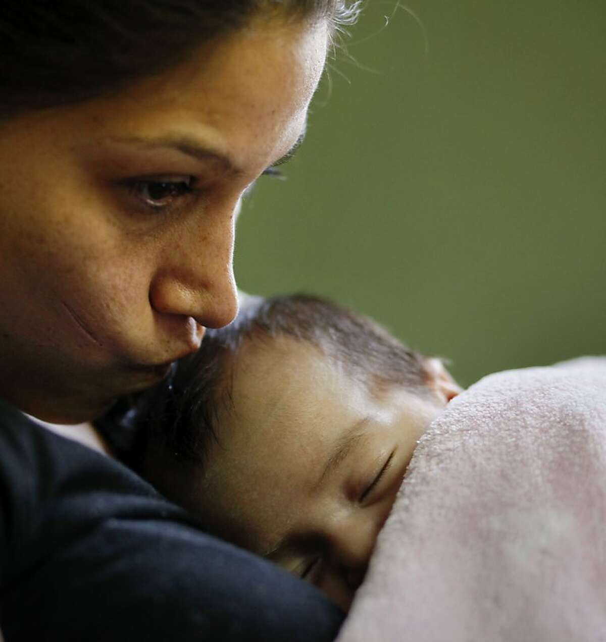Gabrela Baca kisses the forehead of Dourelia, her 6 week old daughter as she watches over her 2 1/2 year old son Douglas, Wednesday March 27, 2013, at Star Community Home, which is run by the Catholic Charities in San Francisco, Calif.