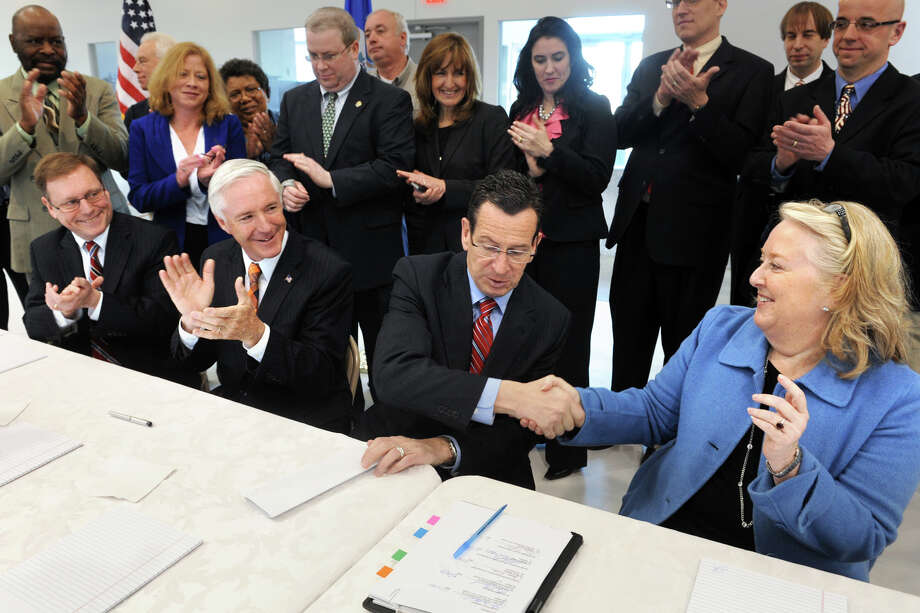 From left, Stratford Mayor James Harkins and Bridgeport Mayor Bill Finch applaud as Governor Dannel Malloy shakes hands with Mary Walsh, FAA Division Manager for Airports, following the signing of documents resolving the long disputed construction of a new runway safety zone at Sikorsky Memorial Airport, in Stratford, Conn., April 17th, 2013. Photo: Ned Gerard / Connecticut Post