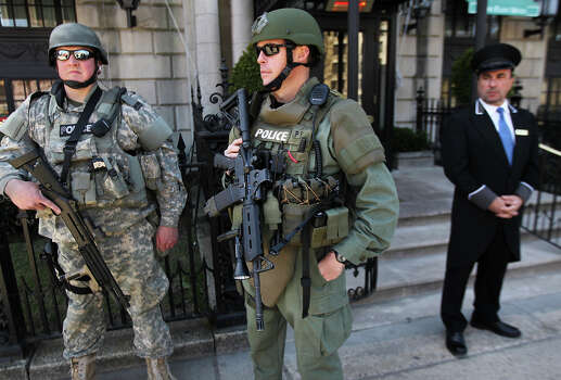 Framingham Police Officer Brian Curtis, Cape Cod SWAT Sgt. Mike Riley and doorman Manuel Alves outside the Eliot Hotel on Commonwealth Avenue. Heightened security in Boston after two explosions went off at the finish line of the 117th Boston Marathon. Photo: Boston Globe, Boston Globe Via Getty Images / 2013 - The Boston Globe
