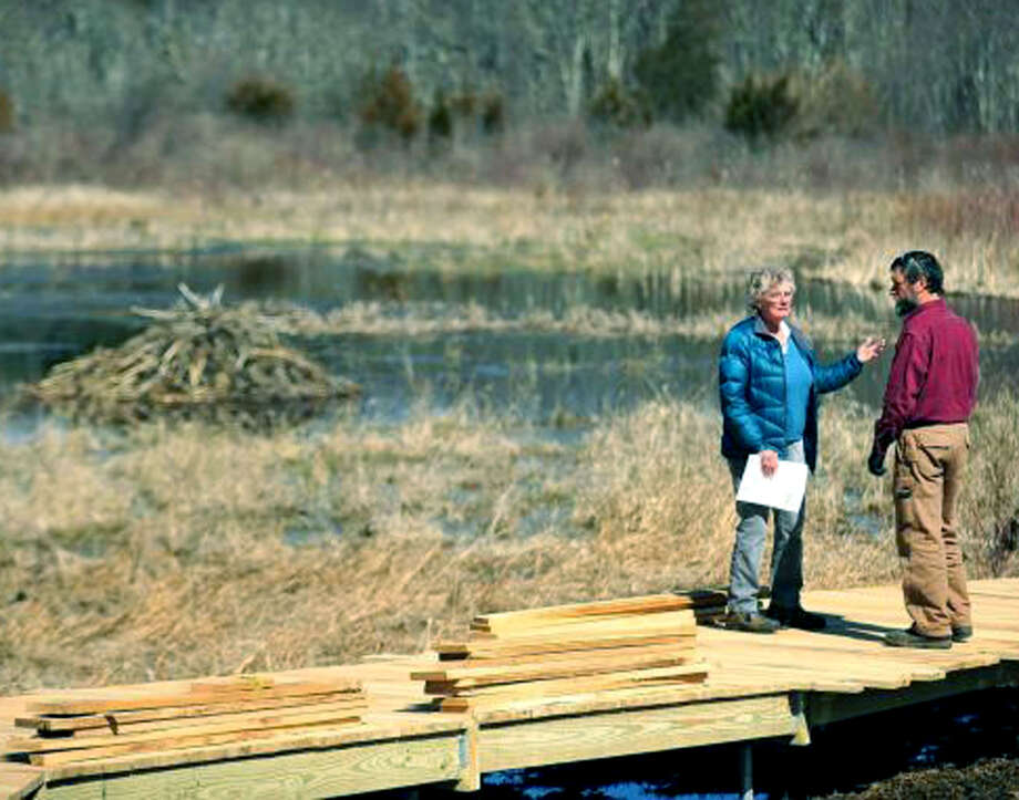 Marge Josephson, the president of the Naromi Land Trust in Sherman, confers with contractor Peter Jensen about the construction of a boardwalk across the Wimisink Swamp Reserve. April 4, 2013 Photo: Michael Duffy