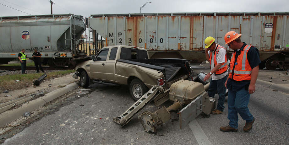 Rail workers and police review the scene of an accident Wednesday April 17, 2013 involving a Ford pickup truck and a northbound Union Pacific freight train on Thousand Oaks between Interstate 35 and Wurzbach Parkway. Police at the scene said the truck was eastbound when the collision took place about 1:00 p.m. . The train's conductor (left, wearing green vest) said the driver of the truck went past the railroad crossing arm and tried to beat the train before it crossed Thousand Oaks. The conductor said the truck clipped the train's lead locomotive and crashed into the post that held the crossing arm. The driver of the truck was not injured. The conductor and the truck's driver would not release their names. The train is bound for Hearne, Texas. Photo: John Davenport / Express-News