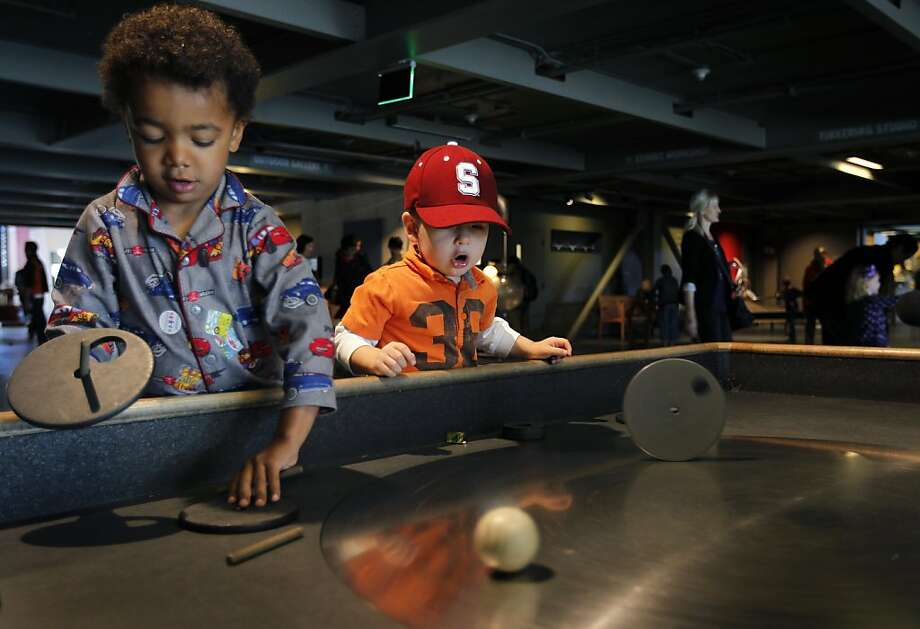 Axel Palms (left), 3, and Aiden Lombardo, 2, spin objects on a steel turntable on the opening day of the new Exploratorium science museum at Pier 15 in San Francisco, Calif. on Wednesday, April 17, 2013. Photo: Paul Chinn, The Chronicle