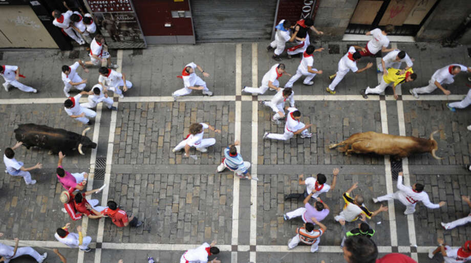 Participants run in front of Torrehandilla-Torreherberos' bulls during the last San Fermin Festival bull run, on July 14, 2012, in Pamplona, northern Spain. The festival is a symbol of Spanish culture that attracts thousands of tourists to watch the bull runs despite heavy condemnation from animal rights groups.      TOPSHOTS/AFP PHOTO/ANDER GILLENEAANDER GILLENEA/AFP/GettyImages Photo: ANDER GILLENEA, AFP/Getty Images / AFP ImageForum