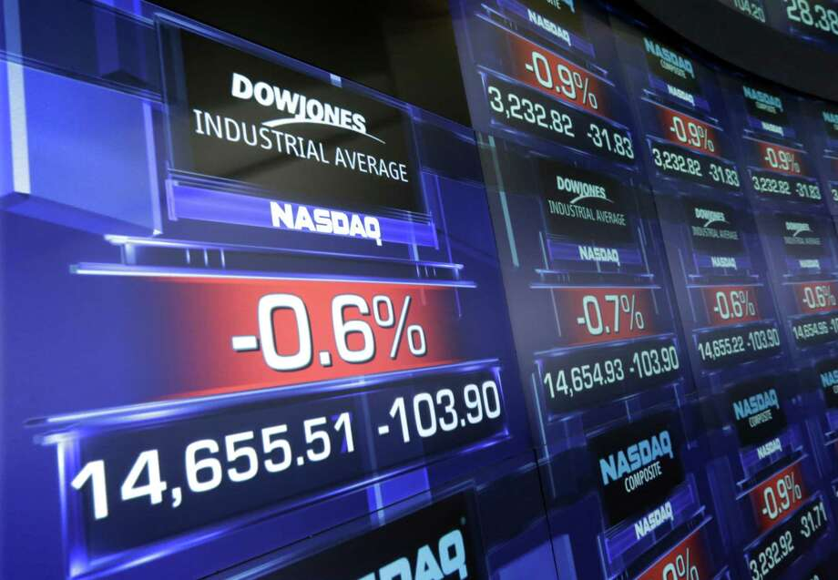 Screens at the Nasdaq MarketSite, in New York's Times Square,  show the Dow Jones industrial average shorthly after the opening bell, Wednesday, April 17, 2013.  Disappointing earnings reports and falling energy prices pushed stock prices lower in early trading on Wall Street Wednesday. (AP Photo/Richard Drew) Photo: Richard Drew