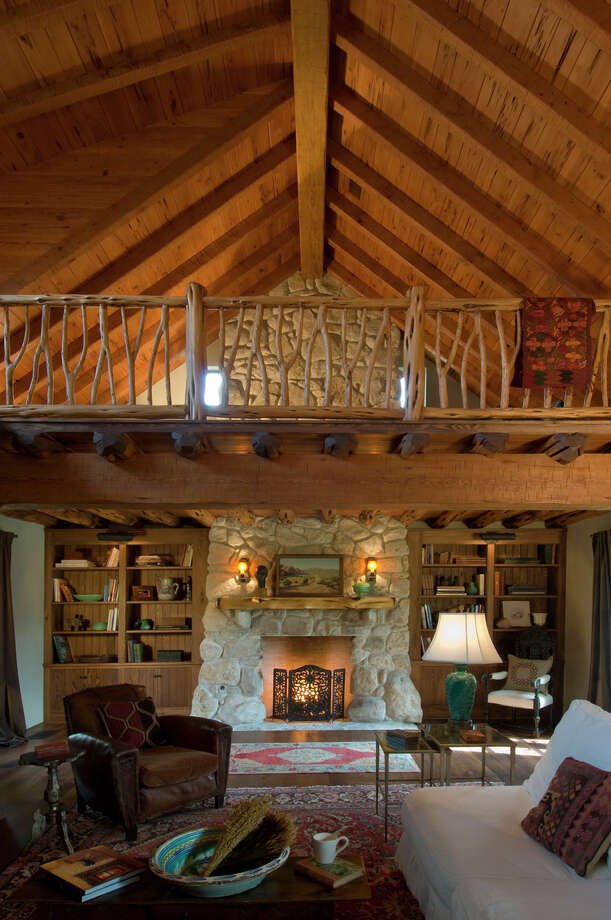 Clockwise from top: The Hill Country ranch house was designed by Michael Imber and is owned by a famous country musician. The highlight of the original floor plan was the two-story living space and stone fireplace. There are four and a half bathrooms in the home. The kitchen's original cedar cabinets were modernized with oversized wrought iron hinges. Photo: Paul Hester, Photographer