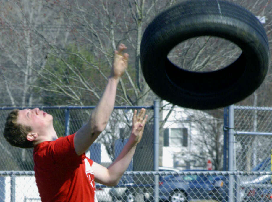 Green Wave veteran Jared Novicky flips a tire to help develop his potential for the throwing events for New Milford HIgh School boys' track, April 2013 Photo: Norm Cummings