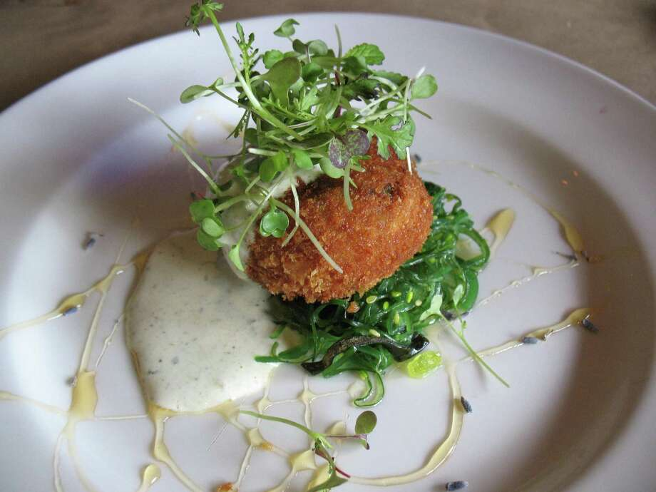Crisp lump crabcake is served with wakame salad, toasted tomatillo buttermilk dressing and a honey drizzle. Photo: Jennifer McInnis / San Antonio Express-News