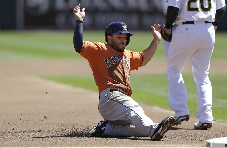 Jose Altuve slides into third base during the first inning. Photo: Jeff Chiu, Associated Press