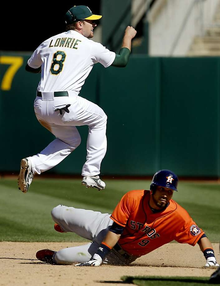 Jed Lowrie hung in the air over Marwin Gonzalez on the double play that ended the game. The Oakland A's against the Houston Astros Wednesday April 17, 2013 at O.co Coliseum. Photo: Brant Ward, The Chronicle