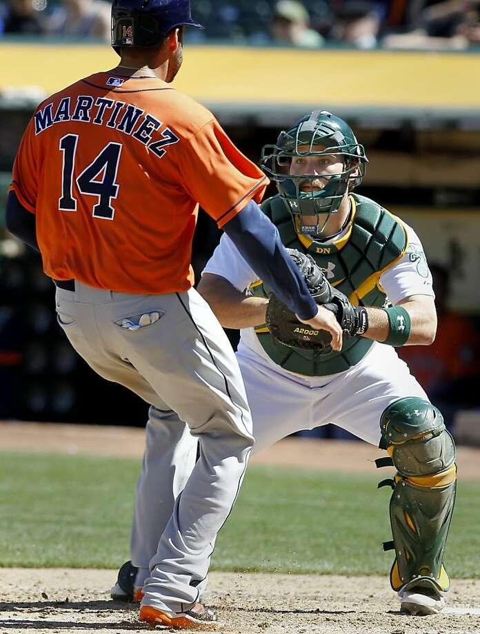 J.D. Martinez is easily tagged out by the A's Derek Norris in the 7th inning. The Oakland A's against the Houston Astros Wednesday April 17, 2013 at O.co Coliseum. Photo: Brant Ward, The Chronicle