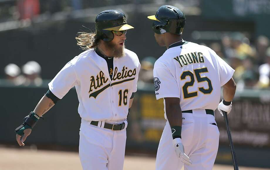 Oakland Athletics' Josh Reddick (16) celebrates after scoring with Chris Young (25) during the first inning of a baseball game against the Houston Astros in Oakland, Calif., Wednesday, April 17, 2013. (AP Photo/Jeff Chiu) Photo: Jeff Chiu, Associated Press