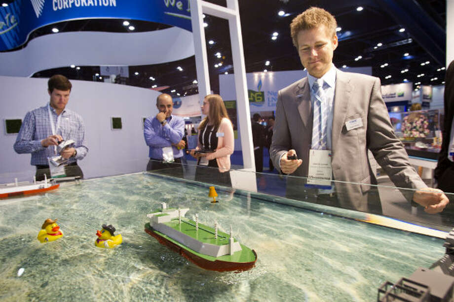 Hilton Butchard, left, takes a turn steering a model LNG ship at the RWE Supply and Trading booth as Gregor Teicher times his run during the 17th International Conference & Exhibition on Liquefied Natural Gas at the George R. Brown Convention Center Wednesday, April 17, 2013, in Houston. Photo: Brett Coomer, Houston Chronicle