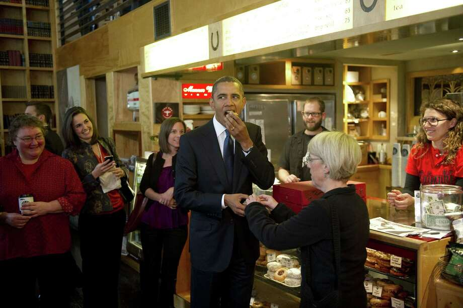 "President Obama visited Top Pot's Belltown store in 2010, where he bought a couple dozen and ate what looked like a glazed old-fashioned. But he quickly cautioned, ""You can't eat these everyday."" Photo: JIM WATSON, AFP/Getty Images / 2010 AFP/Getty Images"
