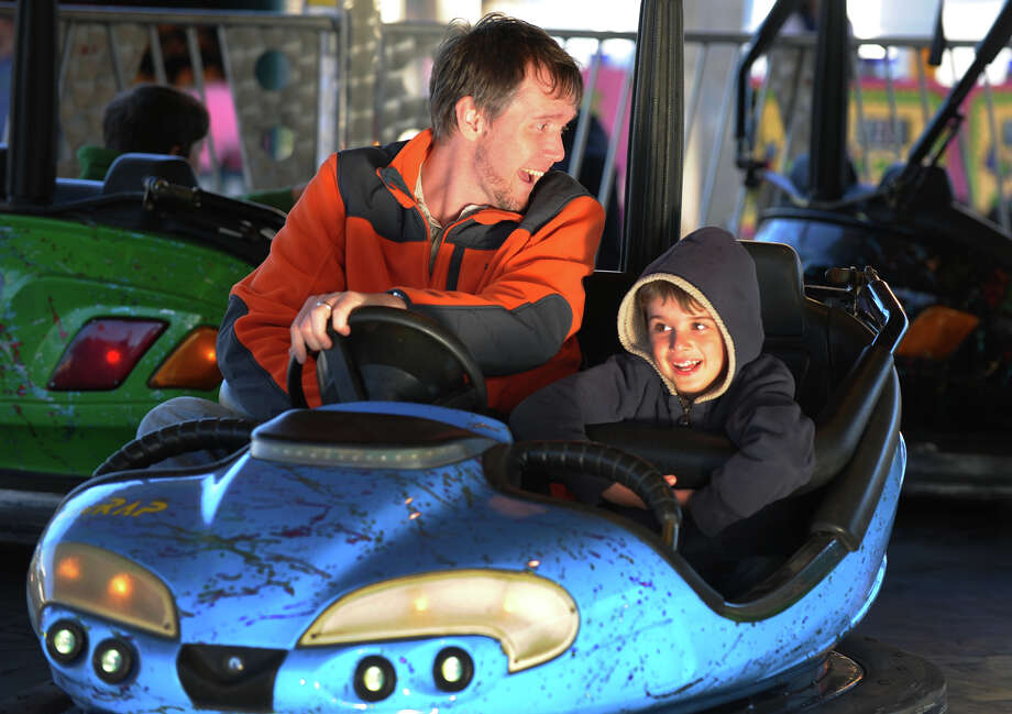 Jason Miller and his son Owen, 6, enjoy the bumper car ride during the Trumbull Rotary Club Carnival at Hillcrest Middle School in Trumbull, Conn. on Wednesday April 17, 2013. The carnival continues through Sunday April 21st. This year, money raised will go towards building a home in Bridgeport for a vet's family through the work by the Trumbull Rotary Club and Habitat for Heroes. More information can be found at www.trumbullrotary.org and www.habitatcfc.org. Photo: Christian Abraham / Connecticut Post