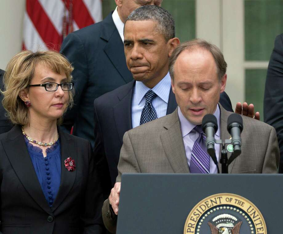 President Barack Obama arrives to participate in a news conference in the Rose Garden of the White House, Wednesday in Washington, about measures to reduce gun violence. With Obama is former Rep. Gabby Giffords, left, and Mark Barden, the father of Newtown shooting victim Daniel. Photo: Carolyn Kaster, STF / AP