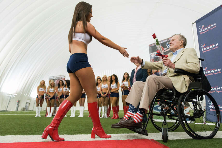 Former President George H.W. Bush presents a rose to a newly announced Houston Texans cheerleader during a ceremony announcing the new squad at the Texans training facility.  The new squad will debut at the Texans' draft party at Reliant Stadium on April 25. Photo: Smiley N. Pool, Houston Chronicle / © 2013  Houston Chronicle