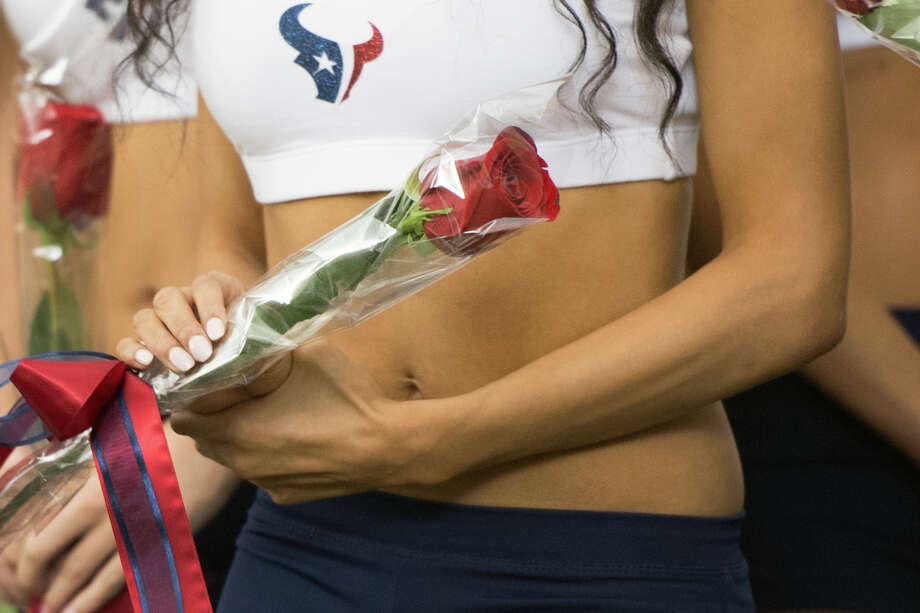 A new Houston Texans cheerleader holds a rose presented to her by former President George H.W. Bush, Photo: Smiley N. Pool, Houston Chronicle / © 2013  Houston Chronicle