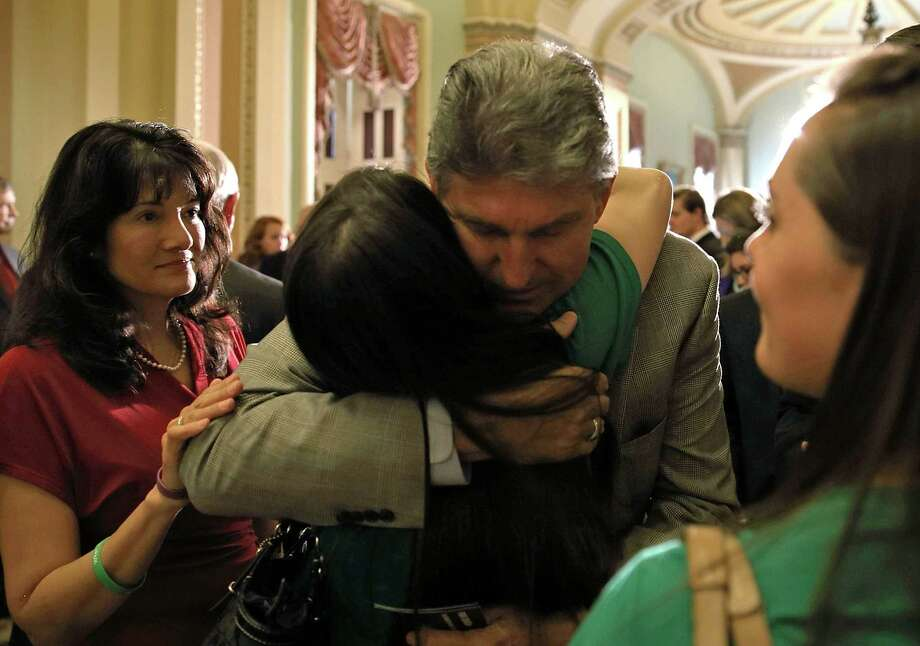 WASHINGTON, DC - APRIL 17:  U.S. Sen. Joe Manchin (D-WV) (3rd L) hugs Sandy Hook victim Vicki Soto's sister Carlee Soto (2nd L), as Sandy Hook victim Dawn Hochsprung's daughter Erica Lafferty (R); and Tucson, Arizona, shooting victim Christina Taylor Green's mother Roxanna Green (L) look on after a vote on the Senate floor April 17, 2013 on Capitol Hill in Washington, DC. The Senate rejected a proposal by Sens. Joe Manchin (D-WV) and Pat Toomey (R-PA) to expand background checks on firearms purchases and to close the so-called gun-show loophole.  (Photo by Mark Wilson/Getty Images) Photo: Mark Wilson