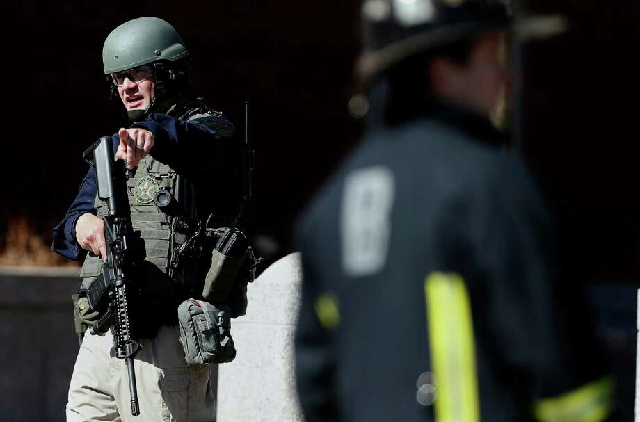 A heavily armed United States Marshall stands guard outside the Moakley Federal Court House in Boston after the building was evacuated, Wednesday, April 17, 2013.  The U.S. Marshals Service in Washington says the courthouse was evacuated due to a bomb threat. Spokeswoman Nikki Credic-Barrett says authorities are conducting a security sweep. (AP Photo/Michael Dwyer) Photo: Michael Dwyer