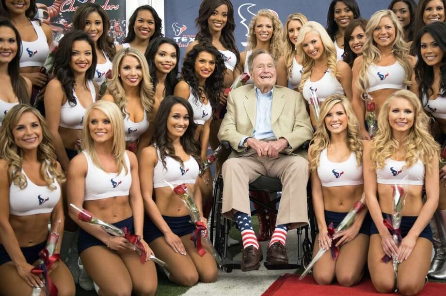 Former President George H.W. Bush poses for a group photo with the newly announced Houston Texans cheerleaders during a ceremony announcing the new squad at the Texans training facility on Wednesday, April 17, 2013, in Houston.  Out of around 900 women who tried out, 34 were selected.