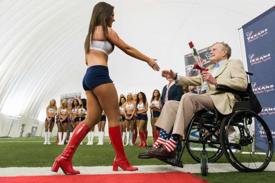 Former President George H.W. Bush presents a rose to a newly announced Houston Texans cheerleader during a ceremony announcing the new squad at the Texans training facility.  The new squad will debut at the Texans' draft party at Reliant Stadium on April 25.