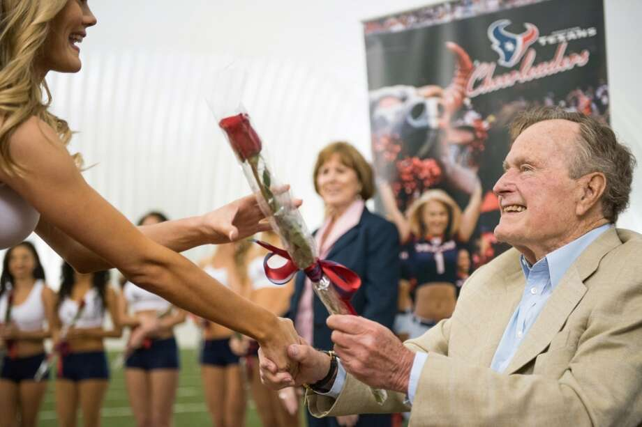 Former President George H.W. Bush presents a rose to a newly announced Houston Texans cheerleader during a ceremony announcing the 2013 squad at the Texans training facility.